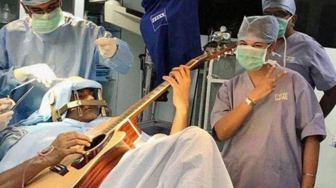 یک نوازنده هندی در حالیکه در اتاق عمل تحت جراحی بود، گیتار نواخت تا برای درمان گرفتگی غیرارادی عضلات انگشت هایش به پزشکان کمک کند.