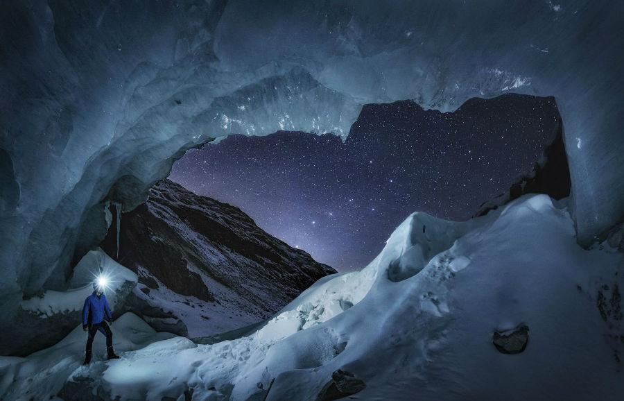 عکاسی که در دروازه غار یخی در انگادین در کشور سوئیس ایستاده و مشغول عکاسی از مجمع الکواکب Big Dipper است.