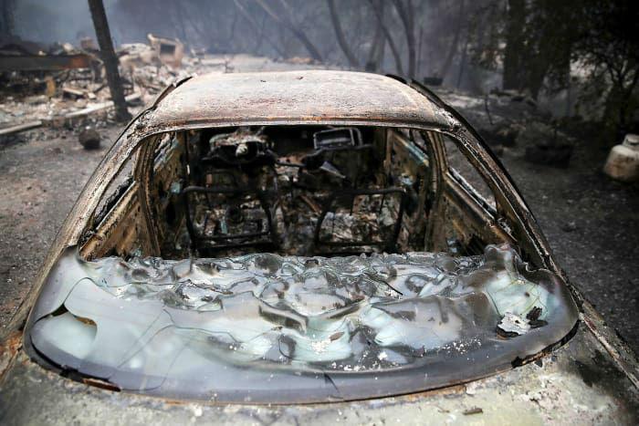 تصویر خودروی سوخته شده در کنار خانه ای که در اثر آتش سوزی جنگل های کالیفرنیا تخریب شده است. 28 تیر.
