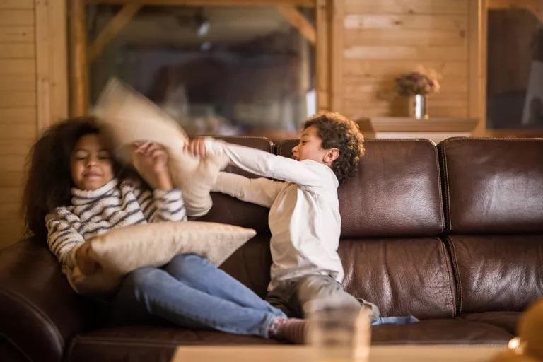 african american siblings having fun during a pillow fight at home چطور از حسادت فرزندان به یکدیگر کم کنیم ؟