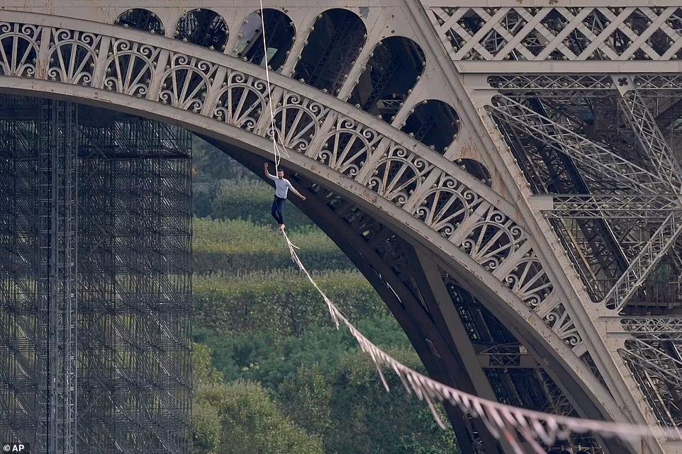 یک بندباز فرانسوی در حالی که روی یک طناب در ارتفاع 200 فوتی راه می رفت، از روی طنابی که از برج ایفل کشیده شده بود گذشت